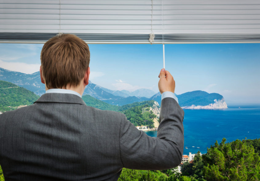 Businessman is looking through the window with sea view