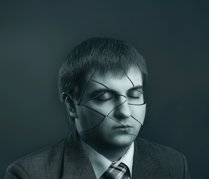 Businessman head with cracks on his face on grey background